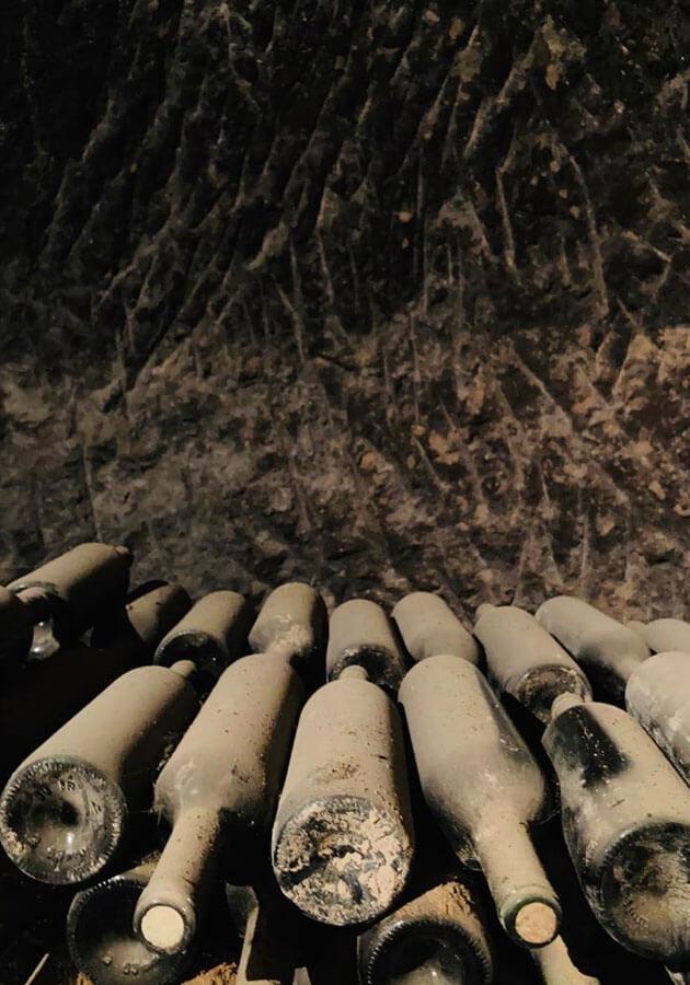 Viejas botellas en el calado de la bodega tradicional de Queirón en Quel